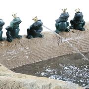 Frösche auf Kalksteinbrunnen